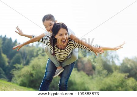 Love playing together. Charming merry woman holding her little daughter on her back, giving her a piggyback ride and spreading hands to the sides like wings