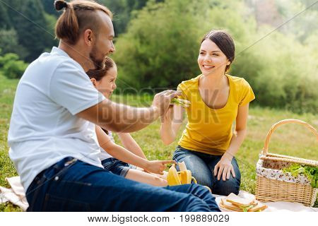 Here you go. Gorgeous young woman giving a sandwich to her beloved husband while having a picnic with her family in the sun-drenched meadow