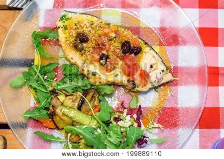 Swordfish stake with olive oil and vegetables served in restaurant. Red and white squares style table. Upside view