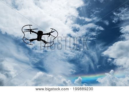 Silhouette drone flying on blue sky with rainbow