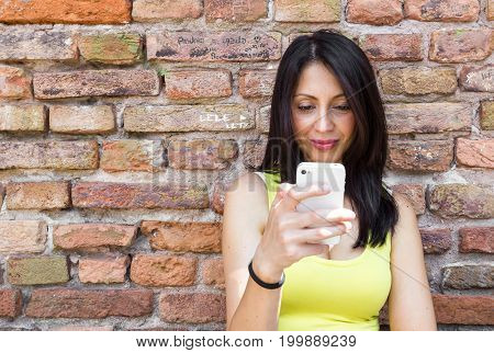 Young brunette woman looking at her smartphone. Behind her is a red stone wall.