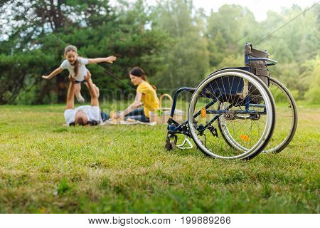 Play of imagination. The focus being on a wheelchair of a happy young man lifting up his little daughter spreading her hands as if being an airplane while being on a picnic