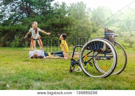 Power of imagination. Happy young man with disabilities lying on grass and lifting up his cheerful daughter as being an airplane while his wheelchair standing in the foreground