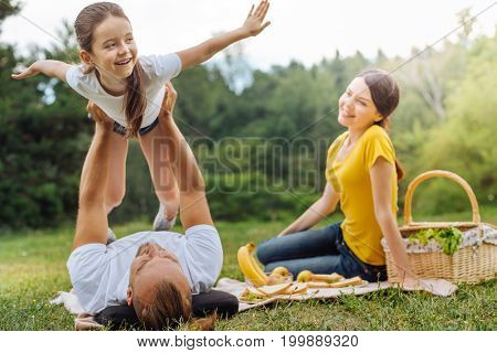 Happy parents. Pleasant young man lifting up his little girl in the air and she spreading her hands like wings while her mother looking at them with happiness