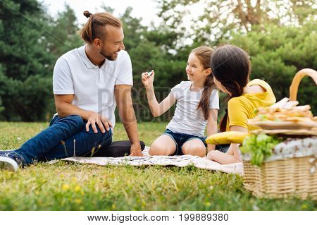 Look what I have. Pleasant petite girl showing a piece of a puzzle to her smiling father while doing a jigsaw together with family on a picnic