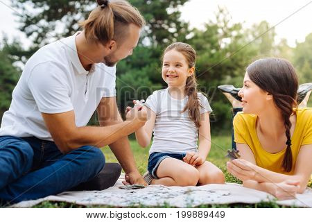 There you go. Caring young father giving his charming little daughter a missing piece of puzzle while they doing it all together on a picnic