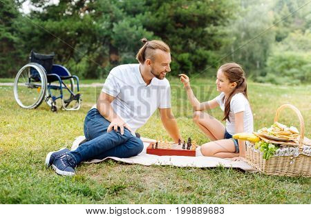 Curious child. Adorable little girl asking her father about chess figures, figuring out about the game on a picnic, while fathers wheelchair standing in the background