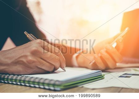 Business Man Using Smartphone, Laptop Computer And Note Some Data On Notepad With Pen