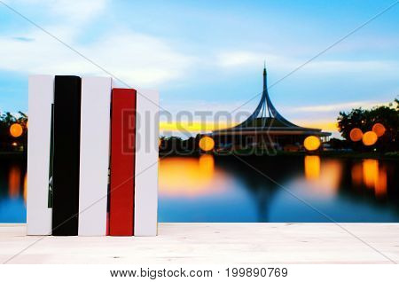 hardback book on wooden shelf or desk no labels blank spine with blurred image of Twilight at Suanluang RAMA IX Public Park and botanical garden in Bangkok Thailand bokeh and reflection on water
