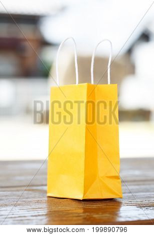 a yellow paper bag on the table on light blurred background