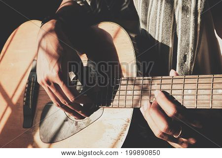 Handsome young men playing guitar with vintage filter