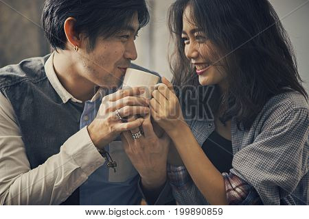 couple of asian younger man and woman happiness emotion with hot coffee cup in hands
