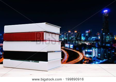 stack hardback book on wood shelf or desk no labels blank spine with blurred image of urban city night light background education back to school and business concept color tone effect copy space