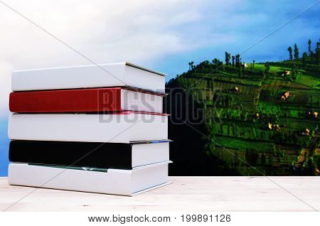 hardback book on wood shelf or desk no labels blank spine with blurred image of village upon the clouds on top view from Bromo indonesia education back to school and landscape concept copy space