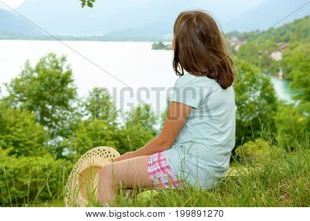 a pretty pre teen girl sitting in grass back view lake in background