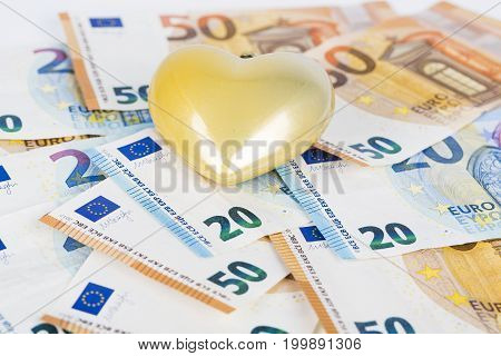 Yellow heart on euro banknotes bills. love and money