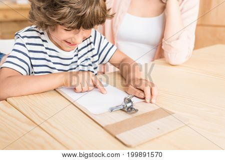 happy little boy pointing at blank paper on clipboard