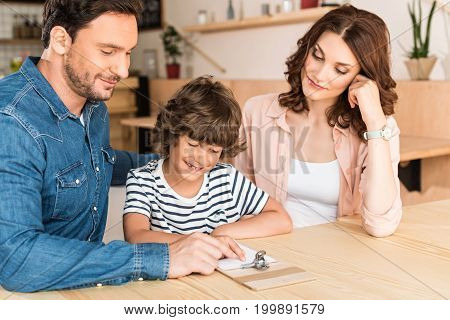 Beautiful Young Family In Cafe Looking At Paycheck