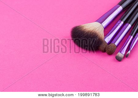 Set of makeup brushes on pink background. Top view point flat lay.