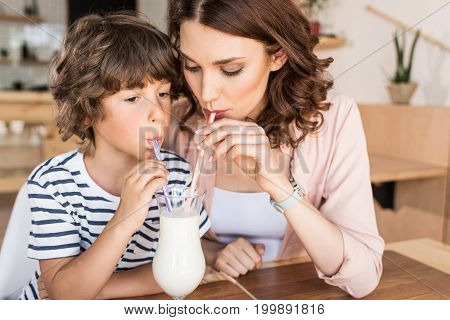 Mother And Son Drinking Milkshake Together In Cafe