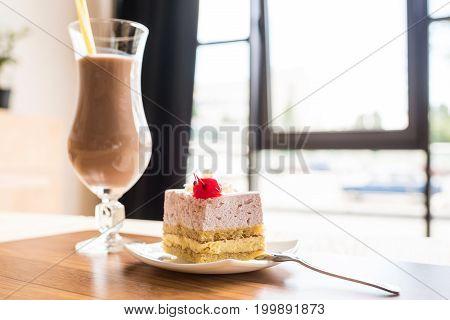 Tasty Piece Of Cake And Glass Of Milkshake In Cafe