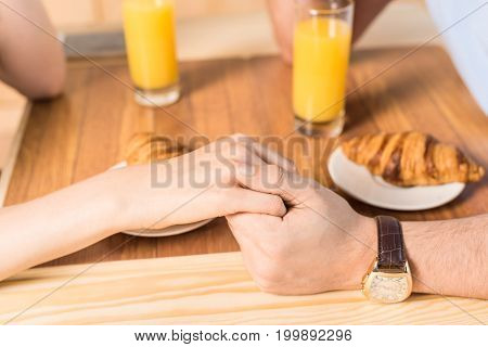 Cropped Shot Of Couple Holding Hands In Cafe With Glasses Of Juice And Croissants
