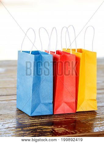 Colorful paper bags on the table on light blurred background