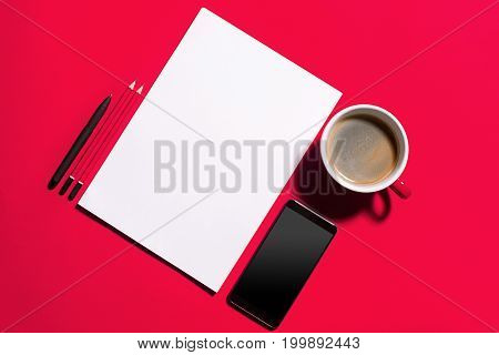 Modern red office desk table with smartphone and cup of coffee. Blank notebook page for input the text in the middle. Top view