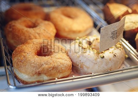 Coffee shop window with baked food pastries. Closeup macro group of many round fresh organic doughnuts in basket with white paper