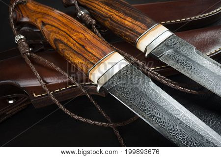 Hunting knife from Damascus mosaic with mammoth tusk on a black background. Leather Sheath Handmade