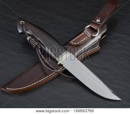 Hunting knife with leather sheaths handmade on a black background
