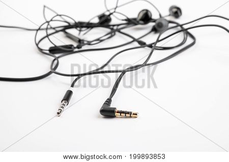 Two Black Headphones Lie On A White Isolated Background. Horizontal Frame