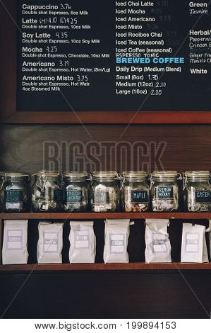 Interior of coffee shop. Wooden board with names of coffee hot and cold drinks prices. Glass jars with tea bags on shelves. Toned with retro vintage film effect filters.