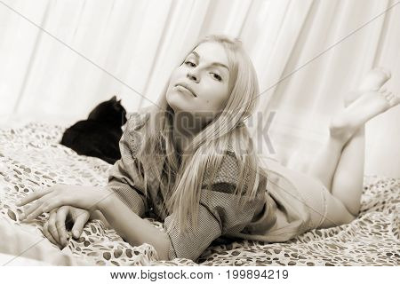 Woman Lying At The Bed With Balck Cat.