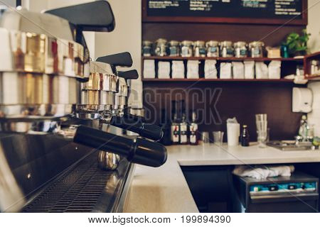 Professional coffee maker. Interior of coffee shop. Closeup of coffee machine in cafe. Toned with film effect filters.