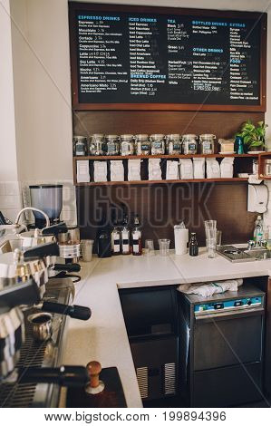 Interior of coffee shop. Wooden board with names of coffee hot and cold drinks prices. Glass jars with tea bags on shelves. Professional espresso coffee maker. Toned with retro vintage filters.