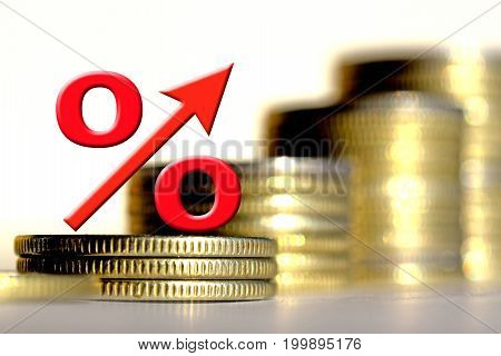 The percent symbol on the background of bars coins . The concept of mortgage lending .