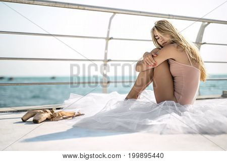 Blonde ballerina with closed eyes sits on the white tutu on the concrete seafront with metal fence. She wears a peach leotard and embraces her legs with the arms. Next to her lying ballet shoes.