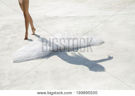 Barefoot ballerina stands on the toes near the white tutu on the concrete surface outdoors. Sun shines on her. Horizontal.