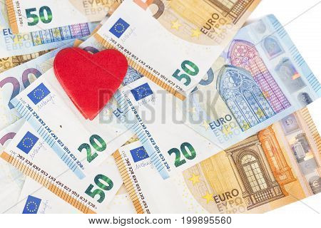 Red heart on euro banknotes bills. On white background. love and money