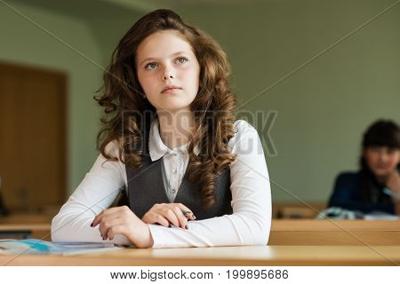 pupils waiting for a lesson, girl looked away and holding a pen
