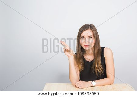 beautiful young businesswoman pointing at copy space isolated on