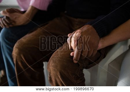 High angle view of senior friends holding hands while sitting on chair in art class