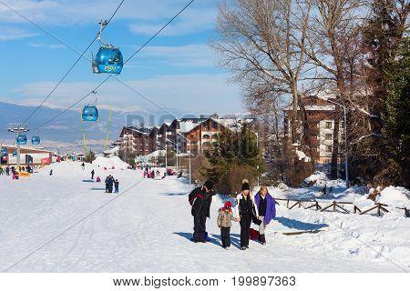 Bansko, Bulgaria - January 13, 2017: Winter ski resort Bansko, ski slope, people skiing and mountains view
