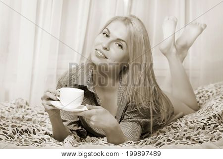 Woman Lying At The Bed And Drinking Coffee And Smiling.