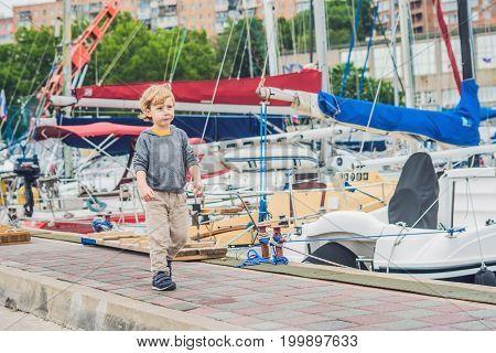 Cute Blond Boy Looking At Yachts And Sailboats