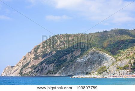 Daylight sunny day view to blue sea and green mountains. Monterosso al Mare, Italy, Cinque Terre.