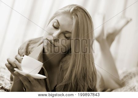 Woman Lying At The Bed And Drinking Coffee.