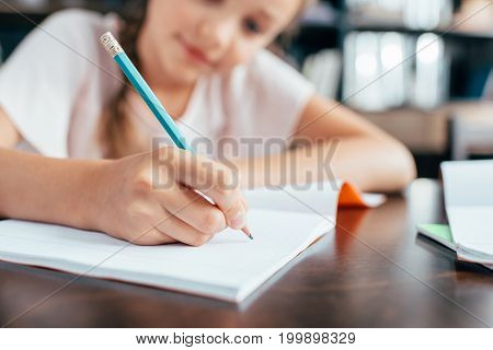 cute cute little girl writing in notebook and doing homework