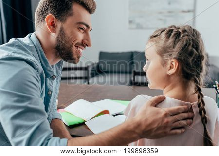 young handsome father helping her daughter with homework